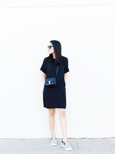 Andy Heart wearing a black t-shirt dress with black side bag and grey slip on sneakers.