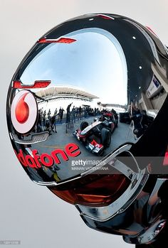 British driver Lewis Hamilton's car is reflected in a McLaren Mercedes technician's helmet in the pit-lane at the circuit ahead of the Formula One Korean Grand Prix in Yeongam on October 13, 2011. AFP PHOTO/ MANAN VATSYAYANA