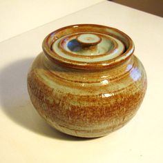 Wheel thrown stoneware lidded storage jar glazed with Coyote PIstachio  glaze then fired in an electric kiln to cone 5 with a 30 minute hold.  Created by Ann Augustin Pottery, Frisco, TX.