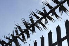 Spiked metal fence from a diagonal angle with blue sky background