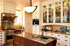 Kitchen with granite counter tops, white cabinets with some stained-glass cabinet doors.