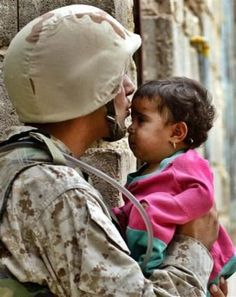 Soldier kissing little girl on the forehead