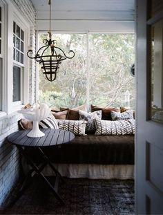 This porch looks a lot like mine with the bricks painted white. Would love a daybed out there.