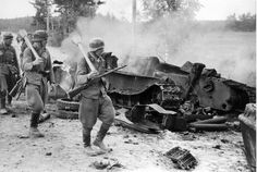 Finnish troops passing by the remains of a destroyed Soviet T-34 at the battle of Tali-Ihantala, 1944