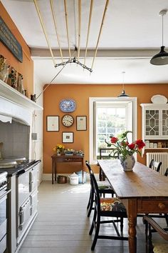 Warm orange kitchen in Kitchen Design Ideas. Country kitchen with Aga, wooden floor and orange walls.