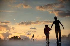 Silhouette d'un père et de sa fille marchant main dans la main sur une surface mouillée reflétant le ciel au couchant. #nice #photo #art Valéry Trillaud #Photographe