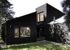 Blackened wood houses with intersecting angled roofs in Argentina by Estudio BaBO.