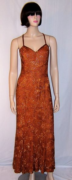 This is a stunning and sleek, burnt sienna colored, glass bugle beaded gown with spaghetti straps that criss-cross in the back, a sweetheart neckline, a back zipper for closure, a fitted bodice, and a slightly flared long skirt. The color is rich and vibrant and the glass beads shimmer when caught by the light. The gown is in excellent vintage condition and would accommodate a modern day Size Small.