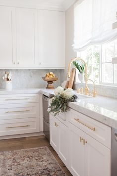 Marble countertops white cabinets and brass fixtures.