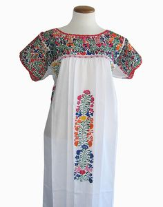Beautifully hand-embroidered Oaxacan wedding dress (San Antonino dress) with multi-colored cotton embroidery in a floral motif on lightweight white cotton, and red lace trim. Short sleeves. See more at: www.elinterior.com