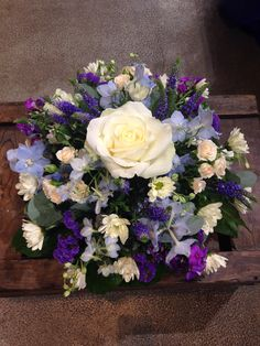 Funeral posy in pretty blues and creams. Including roses and delphinium.