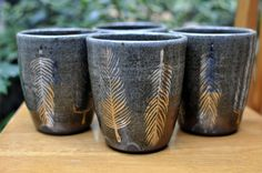 Tumblers for tea adorned with a gleaming gold feather.