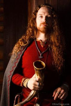 Wealthy Varangian Viking (Tony Arndt). Decorative feather stitch on cloak, rings and bracelets are replicas of Scandinavian and Baltic finds, the Thor's Hammer is a Gotland replica, drinking horn Sutton Hoo replica, and his is shirt diamond twill wool with tablet woven silk trim. Photo by Kira Hagen 2013