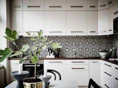 Tiled backsplash against all way cabinets.