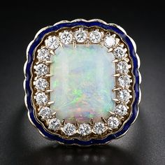 A lavish large scale fun ring featuring a cushion shape opal exhibiting a soothing pallet of pastel green, yellow and blue with flashes of orange. The opal is presented in a retrospective Victorian style mounting, dating back to the 1950s, with a frame of brilliant round diamonds outlined in a scalloped border accented with cobalt blue enamel.
