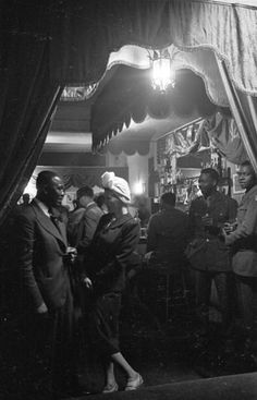 17th July 1943: Proprietor of Frisco's International Club, Piccadilly, London talks to a turbaned girl at the bar. Original Publication: Picture Post - 1486 - Inside London's Coloured Club - pub. 1943 (Photo by Felix Man/Picture Post/Getty Images)