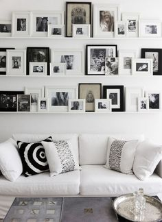 gallery-wall-annika-von-holdt - Gallery wall using shelves from Ikea to rest frames on - Love that you can change out photos so easily.