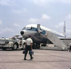 A crew member walks to a Pan American Boeing 707 (ca. 1960)