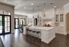 Love the dark wood floor in white kitchen.