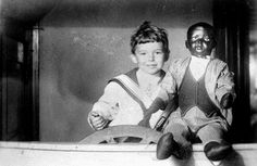 PLAYTHINGS: Three year old white child with an African-American doll (Black minstrel dummy), 1914