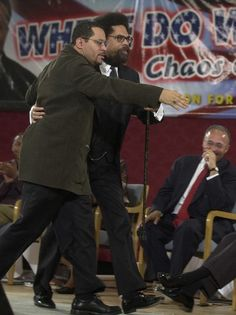 Dr. Michael Eric Dyson, left, escorts Dr. Cornel West across the stage during a symposium at Sharon Baptist Church, in Philadelphia, Pa, Saturday, Feb. 23, 2002.
