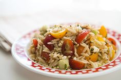 A summer salad of cherry tomatoes, orzo pasta, cucumbers, feta cheese, oregano and green onions, dressed with olive oil and lemon juice.