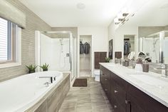 Functional yet stylish, the en-suite in Jayman MasterBUILT's Allure showhome in Secord, Edmonton  is both<br></a>your getaway after a busy day and the ideal space to get ready in the morning. Soft, textured accents match dark,<br/>wood cabinets while a high gloss, horizontal backsplash and accent wall fills the room with light. Wood Cabinets, Neutral Colors, High Gloss, Backsplash, Bathrooms, New Homes, Decorating Ideas, Space, Dark