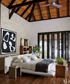 An artwork by Fernando Varela hangs on a coral-stone wall in the master bedroom of singer Marc Anthony and model Shannon de Lima Muñiz's Dominican Republic retreat; the bed is by Roche Bobois, and DM Dominicana designed the tables.