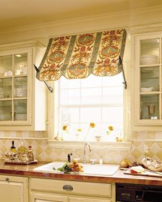 Adding a clever fabric awning accents the window above the sink in this kitchen makeover on a budget. It reinforces a European feel and gives the space dimension. (© Laurey W. Glenn/Southern Living)