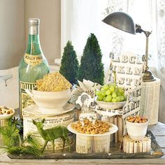 Off-white plates and bowls filled with fruit and nuts sit atop folded books, a covered hatbox, and chipboard sculptures, and greenery adds a winter ambience. Keep the display contained on a vintage tray. Christmas Open House, Christmas Holidays, Christmas Buffet, Christmas Desserts, Vintage Christmas, Christmas Ideas, Party Food Spread, Winter Engagement Party, Winter Parties