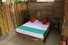 Deluxe mud chalet bedroom with large elegant bed made with rustic wooden poles.