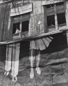 In Manuel Álvarez Bravo's Two Pairs of Legs, 1931, a peeling billboard shows only the legs of its fashion models, laying bare the façade beneath. The image appears flat, but the dark windows suggest an unknown private space lurking behind. Álvarez Bravo depicted with sensitive lyricism and rich symbolism the culture, people, and landscape of his native Mexico. His often mystical images prompted surrealist leader André Breton, who met Álvarez Bravo on a visit to Mexico in 1938, to dub him