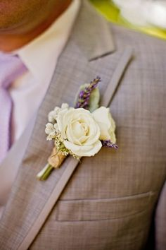 The groom will wear a boutonniere of ivory spray roses, lavender and lamb's ear wrapped in twine with the stems showing