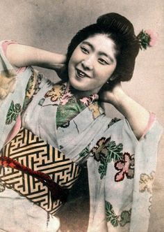 Young woman relaxing in her shibori furisode. Hand-colored photo, Japan, probably about 1900.