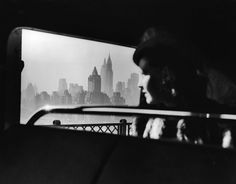 Departing from New York City as she crosses the 59th Street Bridge, a shrouded woman gazes back at the iconic Midtown skyline in 1940.