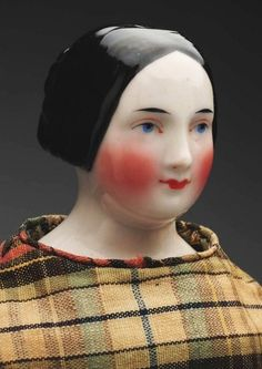 """Lovely German China Lady Doll. : Lot 504.   Shoulder head possibly by A.W. Fr. Kister, with black molded hair, pulled back in waves and draped over the ears with a coiled braid at back """"Fanny Elssler style,"""" oval face with tapered black eyebrows, red eyelid line, black eyelash line, blue painted eyes, closed mouth, rosy cheeks; antique cloth body with separate fingers (soil, 1 finger missing); period silk dress (some deterioration), antique leather boots. Rare, desirable doll.  17"""" tall."""