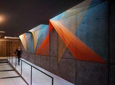 Cette installation d'Inés Esnal dans un complexe résidentiel de Brooklyn crée un prisme avec des cordes élastiques colorées tendues contre un mur qui créent des formes géométriques en se croisant.