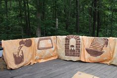 Tent signs . We bought a sheet from our local Goodwill, tie dye with orange color to give them the dessert effect and paint the different tent's signs with brown acrylic paint. Ready to use for our Wilderness Escape VBS.
