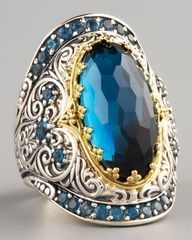"""Oval-cut London blue topaz center and round-cut, prong-set pave details. Scrollwork-carved sterling silver. 18-karat yellow gold setting. Approximately 1""""L. Handcrafted in Athens, Greece."""