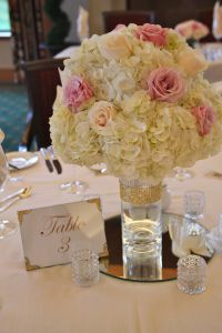 Full globes of hydrangea and blush roses accented with touches of gold for the centerpieces.
