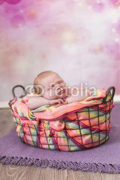 Newborn kleines Mädchen in einem Korb sehr bunt