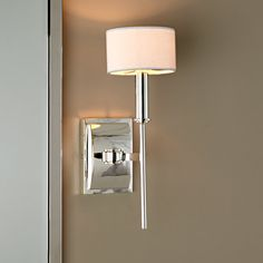 """This sconce is reminiscent of a mid-20th century Italian chandelier. It has a crisp contemporary, yet sophisticated look. The white silk shades are included, but can be removed for another stunning option. This elegant piece is made of solid brass, finished in Polished Chrome. 60 watts. (candle base socket)(14""""Hx5""""Wx7.5""""D)Linen Drum Shade (5""""x5""""x3"""")Backplate: 4"""" x5"""""""