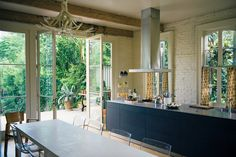 White washed brick, an antler chandelier & a view of the garden from the kitchen in a New Orleans home