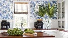 A white kitchen is every bit as crisp with a splash of color on its walls, and tropical bonus points are awarded when it comes in the form of blue-and-white palm wallpaper by Cole & Son.