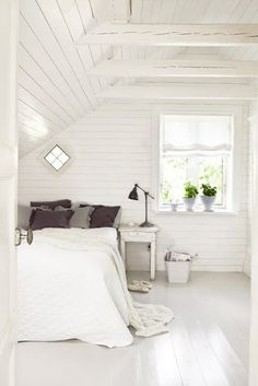 White plank walls and floors. I like the hint of soft brown and grey in the ruffled pillows.
