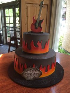 Tiered rock n roll themed birthday cake with flames and electric guitar