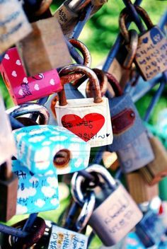 A chain link fence in Seoul. Couples write their names on the locks and toss the key into the river below.