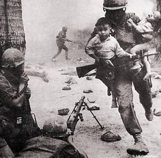 A soldier runs from the battlefield with two small Vietnamese children in his arms. [Vietnam War 1955 - 1975]