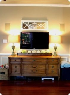 TV wall - substantial stand that gives weight to the space. Interesting mirror above TV makes it feel more decorative. These aren't your colors necessarily, but the shapes are good. Notice the wainscoting behind with the white-on-beige - do you like that?