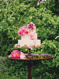 Spring wedding cake adorned with lush pink peonies | Photo by Mollie Crutcher